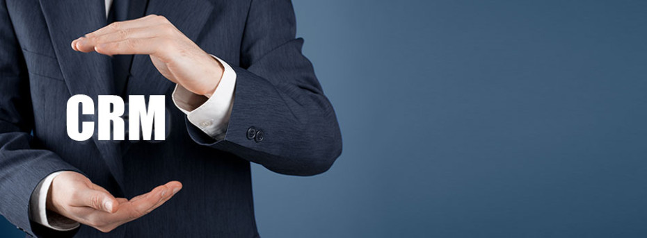 """A business man in a suit holding a floating acronym: """"CRM"""""""